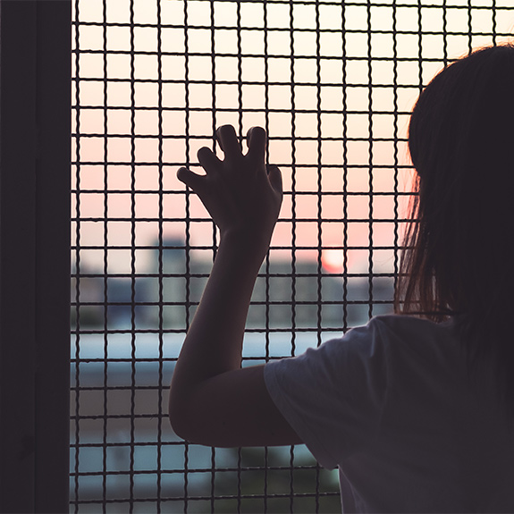Woman leaning against chain link fence